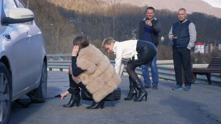 lekke band : two girls changing a car wheel on the side, and the men watching from the side Stockvideo