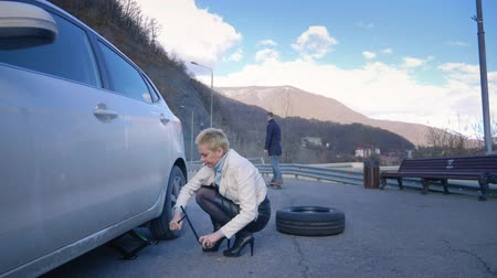 beira da estrada : humor. woman changing a car wheel. a man rides past on electric skate Board. Stock Footage