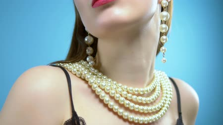 жемчуг : beautiful young girl with pearls and earrings on a blue background