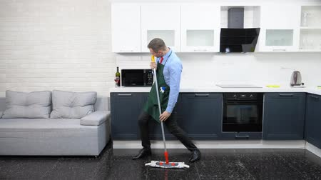 sanitize : handsome man in an apron in the kitchen is dancing with a mop in his hands.