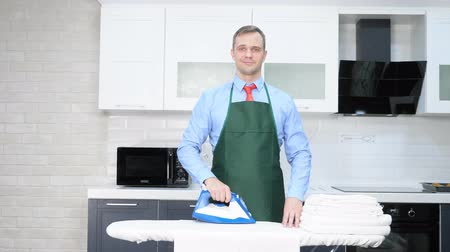 белье : handsome man in a tie and apron ironing linen. cleaning concept Стоковые видеозаписи