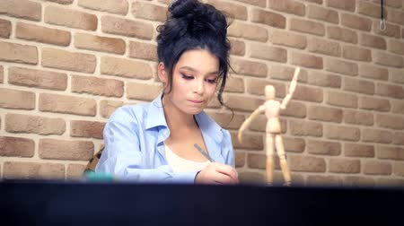 кукла : beautiful brunette girl draws a sketch with a wooden mannequin Стоковые видеозаписи