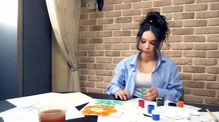 guache : beautiful brunette girl painting with gouache. creative workshop