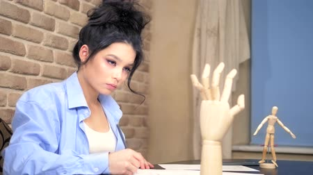 figurka : beautiful brunette girl draws a sketch with a wooden mannequin Dostupné videozáznamy