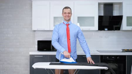 wasserij : vertical shot. handsome man in tie ironing pants. the kitchen of his house Stockvideo