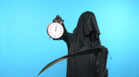수의 : A man in a death suit with a scythe, shows a clock. blue background