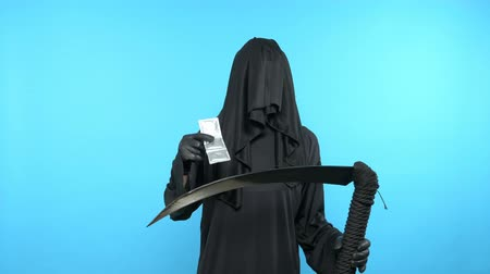 fertility : A man in a death suit with a scythe, shows condoms. blue background Stock Footage