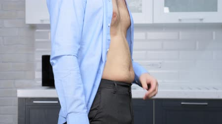 liposukcja : weight loss concept. man hardly fastens his pants, on a thick stomach