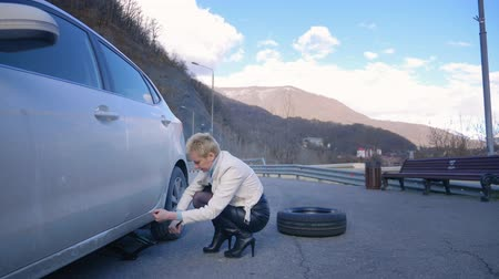 İngiliz anahtarı : beautiful girl changing the wheel of a car parked on the roadside Stok Video