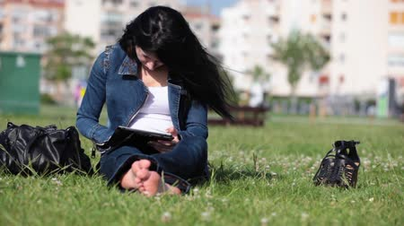 aşağı bakıyor : Study On The Grass.Yound woman holding a pad and studying on the grass .Slider shot.