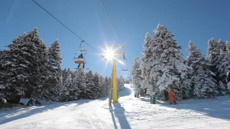 esqui : Sunny day in the snowy mountain and ski lift moves up with skiers.