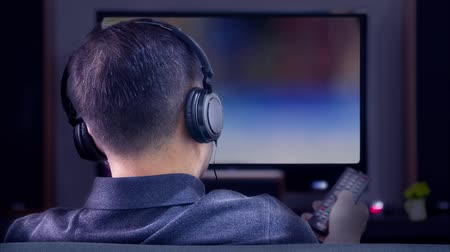 stereoanlage : Back side of an Asian man wearing black headphones in front of blurry out-of-focus television and home entertainment system background