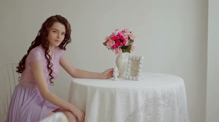 uzun saçlı : Beautiful brunette in a pink dress sits at a table in a beautiful studio HD