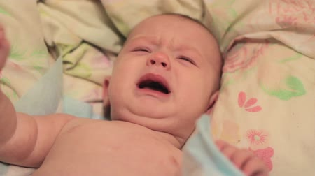 крик : Little baby crying on the bed