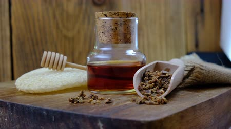 A bottle of propolis tincture and a wooden scoop of propolis granules. Medical preparations bee propolis. Bee glue. Apitherapy. How to treat bee products. Stock Footage