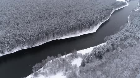 Литва : Aerial - Flying above dark winter river. White trees on the shore