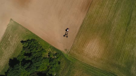 полосатый : Overhead drone shot of tractor in a field.