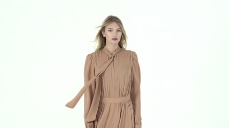 Fashion model in flying beige dress. Slow motion