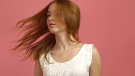 aydınlatmalı : Beautiful teenage girl with red blowing hair and blue eyes on pink background
