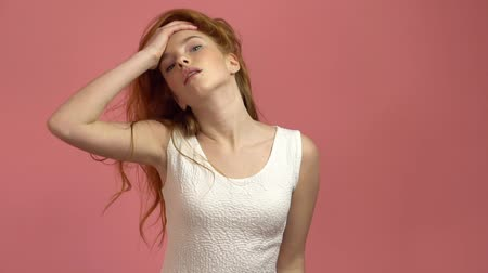 Beautiful teenage girl with red blowing hair and blue eyes on pink background