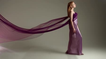 Fashion model in flying purple dress. Slow motion Стоковые видеозаписи