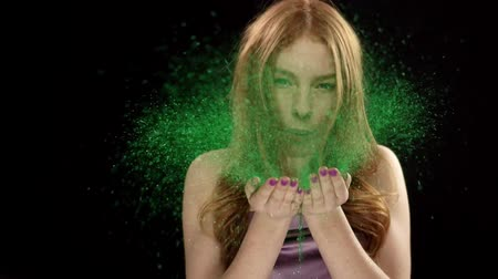 Teen girl with beautiful face and red hair blowing green glitter