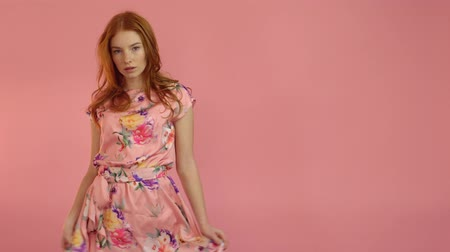 Portrait red-haired fashion model in pink dress on a pink background