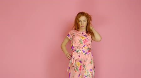kadınlık : Portrait red-haired fashion model in pink dress on a pink background