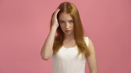 nőiesség : Portrait red-haired fashion model in pink dress on a pink background