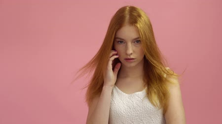 szervezett : Portrait red-haired fashion model in pink dress on a pink background