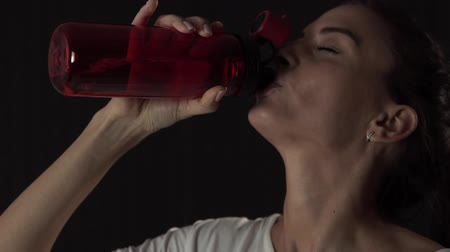 longhair : Slim young woman drinking water after training slow motion Stock Footage