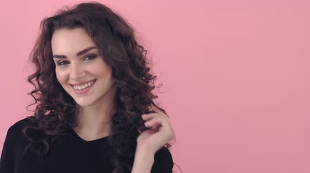 blueeyes : Beautiful fashionable girl with long curly hair in a black T-shirt. Girl in the studio on a pink background.Advertising, hair products, beauty salon, cosmetics, clothing. Fashion, boutique. Pink. Stock Footage