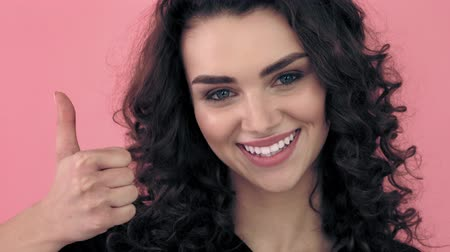 kıvırcık saçlar : Beautiful fashionable girl with long curly hair and snow-white smile in a black T-shirt. Girl in the studio on a pink background.Advertising, hair products, beauty salon, cosmetics, clothing stomatology. Fashion, boutique. Pink.