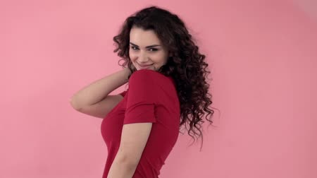 butik : Beautiful fashionable girl with long curly hair in a red T-shirt. Girl in the studio on a pink background.Advertising, hair products, beauty salon, cosmetics, clothing. Fashion, boutique. Pink.