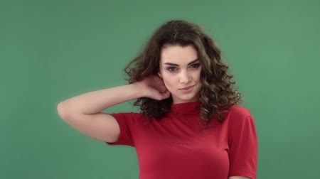 butik : Beautiful fashionable girl with long curly hair in a red T-shirt. Girl in the studio on a green background. Advertising, hair products, beauty salon, cosmetics, clothing. Fashion, boutique. Pink.
