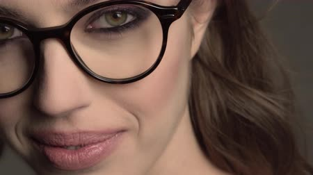model : Indoor portrait of young good-looking girl in round glasses with braces on gray background Stock Footage