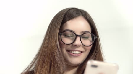 nerd : Young woman in trasparent eyeglasses isolated on on a white background, smiling, with phone