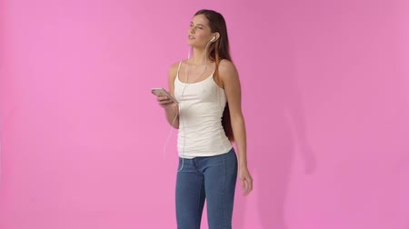 utas : A girl in jeans and a T-shirt listening to music in headphones on a pink background Stock mozgókép