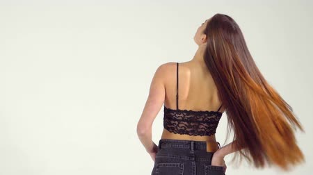 uzun saçlı : A girl with long dark and straight hair waves in a slow motion Stok Video