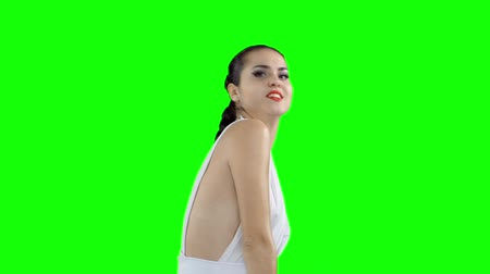 heyecan verici : A girl in a white dress is dancing, on a green screen slow motion