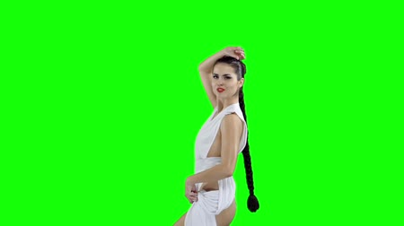 energický : A girl in a white dress is dancing, on a green screen slow motion