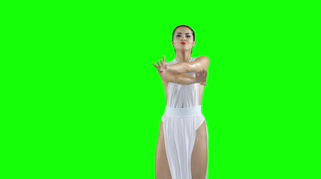 disko : A girl in a white dress is dancing, on a green screen slow motion