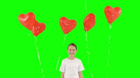 oneperson : Little girl holding bundle of red heart shaped air balloons isolated on green screen. Slow-motion shooting