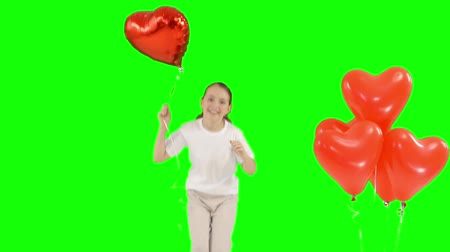 przedszkolak : Little girl holding bundle of red heart shaped air balloons. Bounces up. isolated on green screen. Slow-motion shooting Wideo
