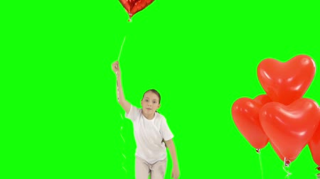 oneperson : Little girl holding bundle of red heart shaped air balloons. Bounces up. isolated on green screen. Slow-motion shooting Stock Footage