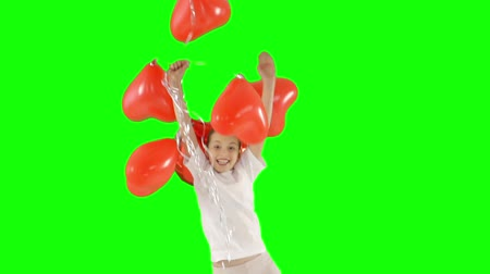 bliskosc : Little girl holding bundle of red heart shaped air balloons. Bounces up. isolated on green screen. Slow-motion shooting Wideo