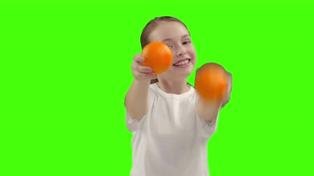 caráter : The little girl holds two oranges and smiles