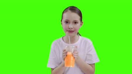 przedszkolak : Nice girl drinking through a straw drink. Green screen