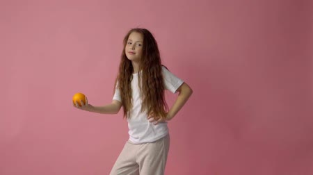 фрукты : The little girl holds orange