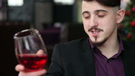kırmızı şarap : A guy with a glass of wine is talking in a restaurant